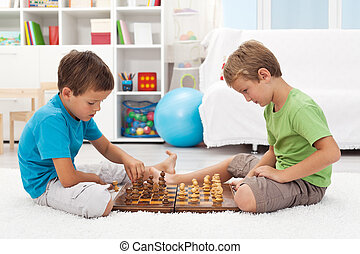 Kids playing chess in their room - Kids playing chess...