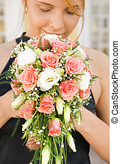 Happy redhead girl smelling bridal bouquet
