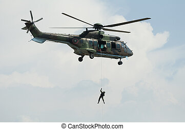 Soldier hanging from a helicopter