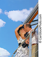 Middle-aged couple kissing on a balcony