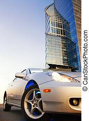 Sport car with office building and clear blue sky behind it