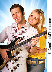 Young musician plays guitar and beautiful blond girl stands...