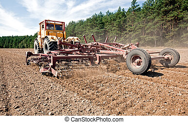 Prepare a field for planting - Harrowing a field with a...
