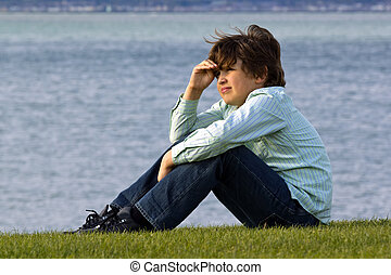 a boy sitting on seacoast and looking in distance