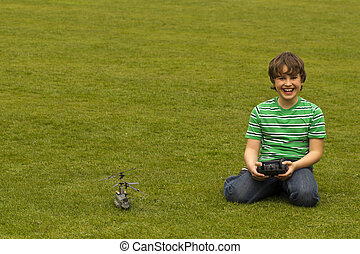 a boy sitting on the grass and playing with a toy- helicopter