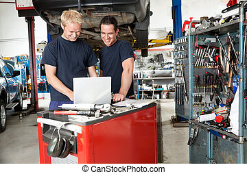 Mechanics with laptop in garage - Mechanics working on...