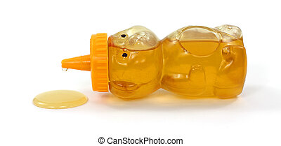 Spilling honey - A honey bear container on its side with...