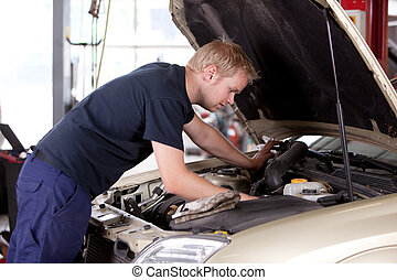 Mechanic Fixing Car - A young mechanic under the hood of a...