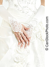 Brides hands with manicure in white lace gloves