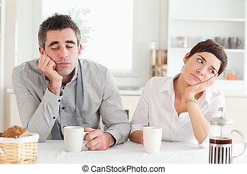 Unhappy couple drinking coffee