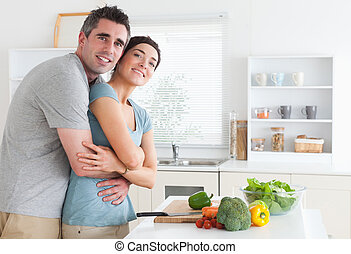 Happy couple hugging in the kitchen