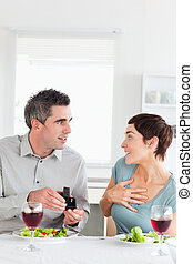 Man proposing to his cute girlfriend in a dining room