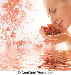 Beautiful young woman with a handful of aromatic berries reflecte