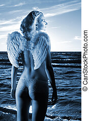 Beautiful angel in a sea at sunset time (toned in blue)