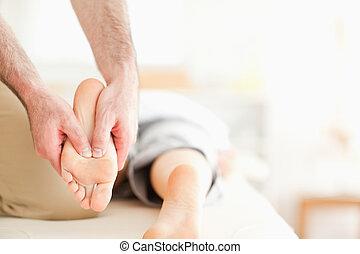 Male masseur massaging a woman's feet in a room