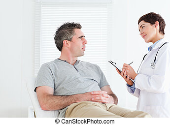 Female doctor talking to a patient in a room