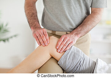 Male Chiropractor massaging a charming womans knee in a room...