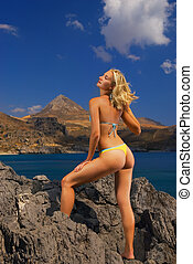 Beautiful blond girl relaxing in mountains near the sea