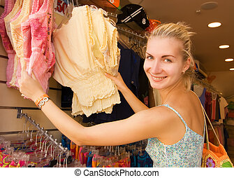 Young beautiful girl buying clothes in a shop