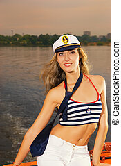 Beautiful girl in captains hat on a yacht