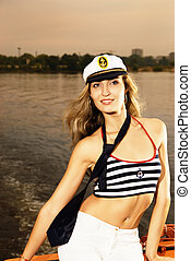 Beautiful girl in captains hat on a yacht toned in sepia