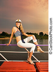 Sexy girl on a yacht at sunset time