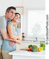 Smiling Man and woman hugging in a kitchen
