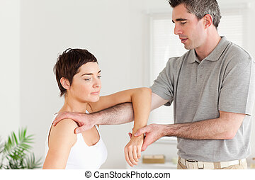 Chiropractor stretching a womans arm in a room
