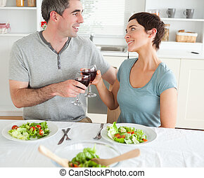 Close up of a cute couple toasting with redwine in a dining...