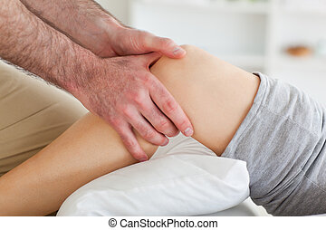 Man massaging a womans knee in a room