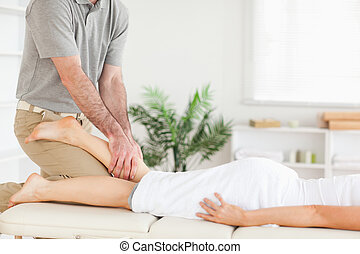 Masseur massages woman's leg - A masseur massages a woman's...