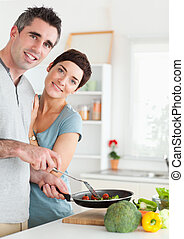Gorgeous Woman and her pan-holding husband looking into the camera in a kitchen