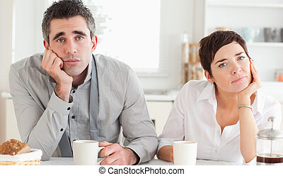 Worn out couple drinking coffee in a kitchen