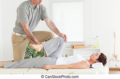 Chiropractor stretches womans arm - A chiropractor stretches...