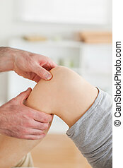 Guy massaging a woman's knee in a room