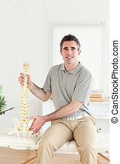 Chiropractor holding a model-spine looking into the camera...