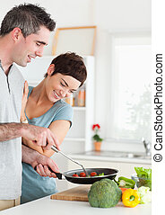Gorgeous Woman looking into a pan her husband is holding in...