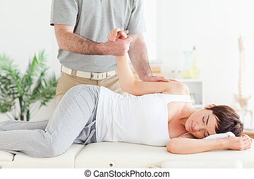 Chiropractor, stretches, female, customer's, arm