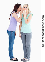 Young woman telling friend a secret