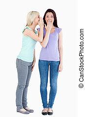 Charming woman telling her friend a secret