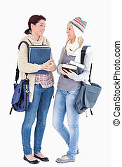 Students with books talking - Two cute female students with...