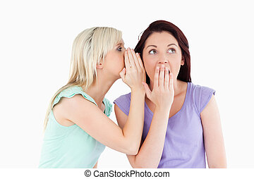 Portrait of a gorgeous woman telling her friend a secret