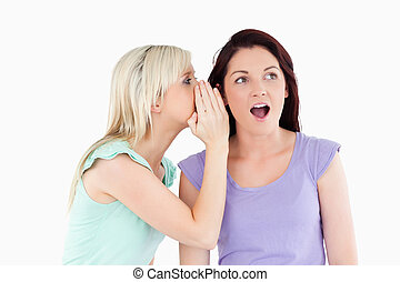 Portrait of a radiant woman telling her friend a secret in a...