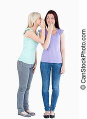 Blond woman telling her friend a secret