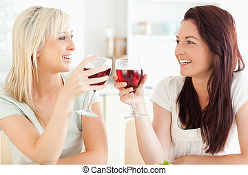 Joyful women toasting with wine in a kitchen