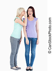 Beautiful woman telling her friend a secret
