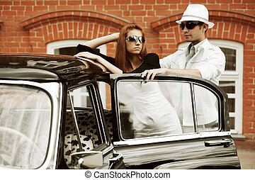 Young couple with a retro car on a city street.