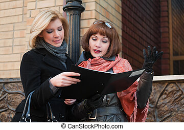 Two young businesswomen with financial reports