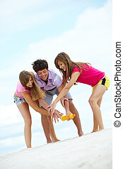 Bottle play - Portrait of laughing teenagers having fun on...