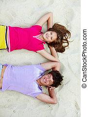 Couple of teens - Above angle of joyful teenage couple lying...